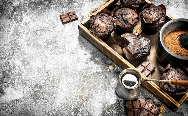 Muffins de chocolate con café caliente en la mesa rústica.