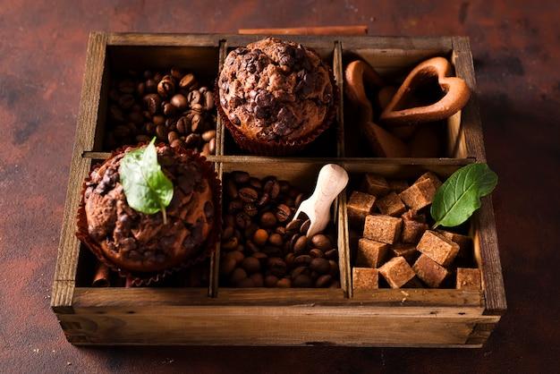 Muffins de chocolate en una caja de madera con granos de café y especias,