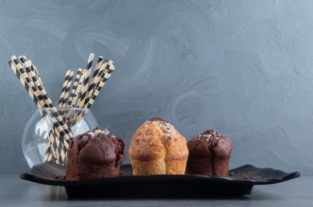 Muffins de chocolate con muffin de nueces sobre un tablero oscuro