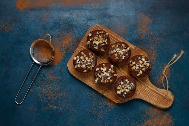 Muffins de chocolate y nueces con una taza de café con nueces sobre una superficie oscura
