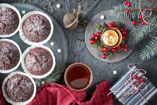 Muffins de chocolate, taza de té, malla de té en gris