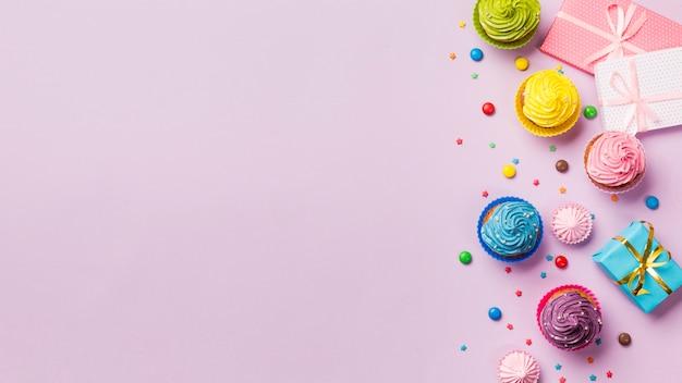 Muffins coloridos y gemas con cajas de regalo envueltas con espacio de copia sobre fondo rosa