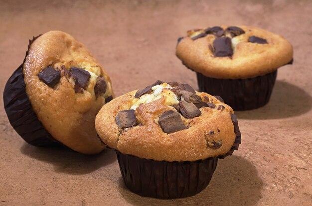 Muffins frescos con chocolate sobre fondo marrón