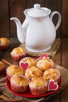 Muffins de frutas con nuez moscada y pimienta de jamaica en una cesta de mimbre sobre una mesa de madera