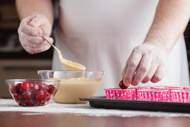 Muffins sin hornear en cajas de muffins de papel en una bandeja para hornear decorada con cherrie