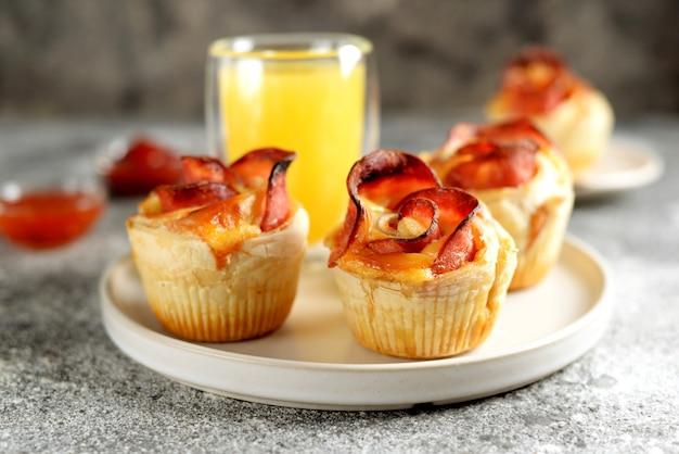 Muffins rosas de hojaldre con jamón y queso sobre una superficie clara
