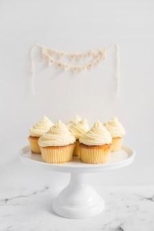 Muffins en la torta blanca de pie contra el fondo blanco