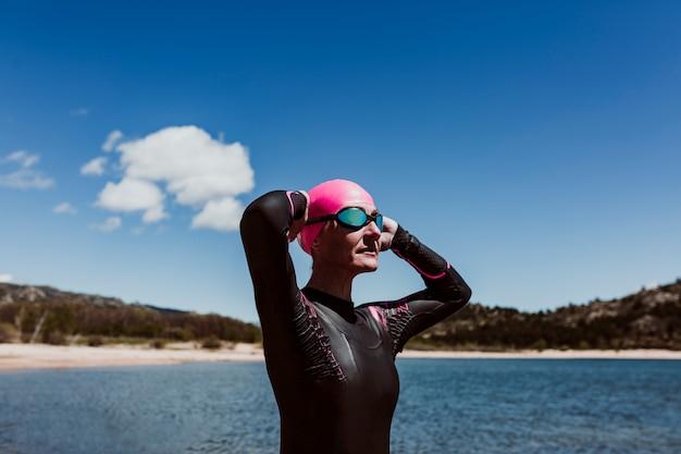 Mujer de unos 40 años vistiendo un neopreno y esperando para nadar en el lago. concepto de triatlón