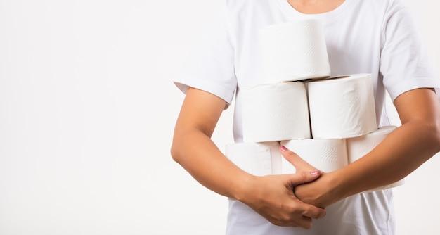 Mujer abarrotando sosteniendo muchos rollos de papel higiénico en brazos en el pecho