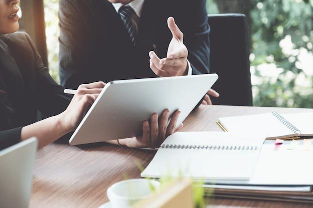 Mujer y abogados de negocios que discuten y que usan la tableta digital en el escritorio de madera en oficina. derecho, servicios jurídicos, asesoramiento, concepto de justicia.