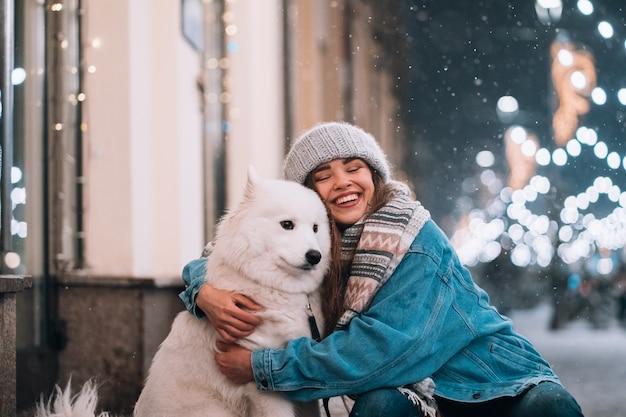 Mujer abraza a su perro en una calle de noche