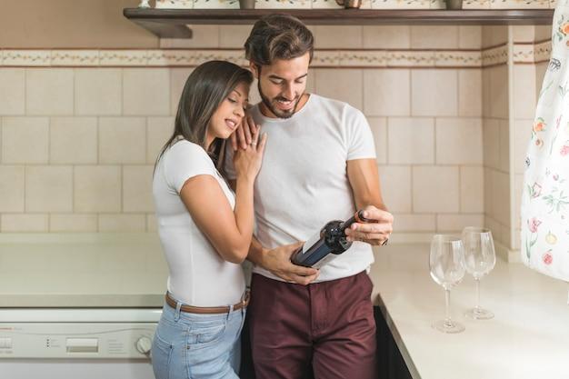 Mujer abrazando novio con botella de vino