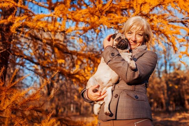 Mujer abrazando perro pug en el parque otoño