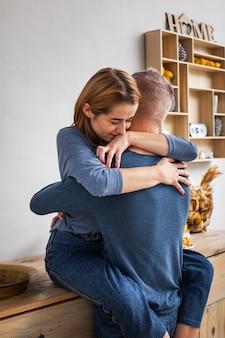 Mujer abrazando a su esposo en la cocina