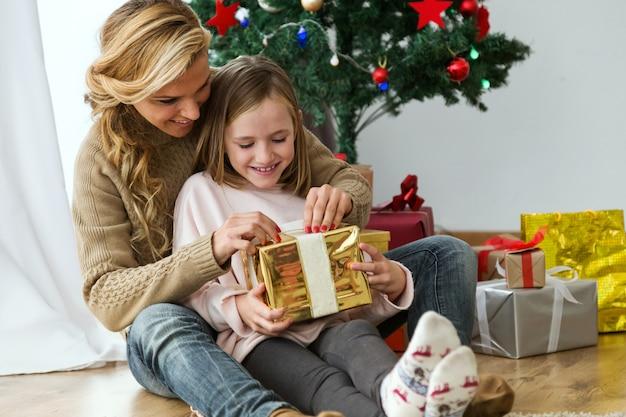 Mujer abrazándo a su hija con un regalo dorado y con regalos de fondo