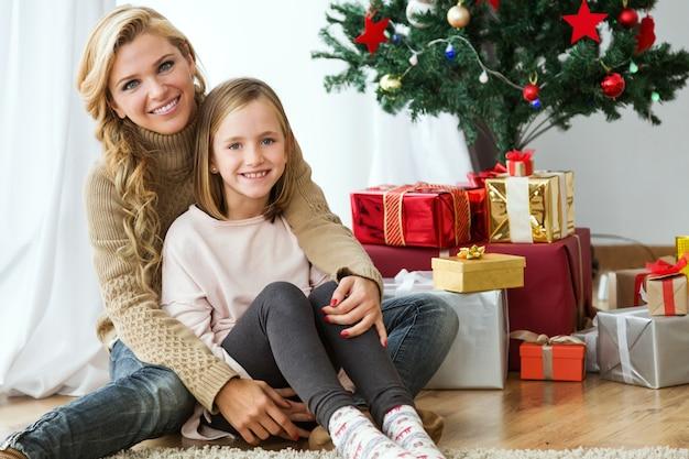 Mujer abrazándo a su hija con regalos de fondo