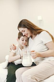 Mujer abrazando a su hijo sosteniendo una jarra con leche.