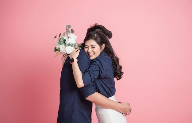 Mujer abrazando a su novio con ramo en mano