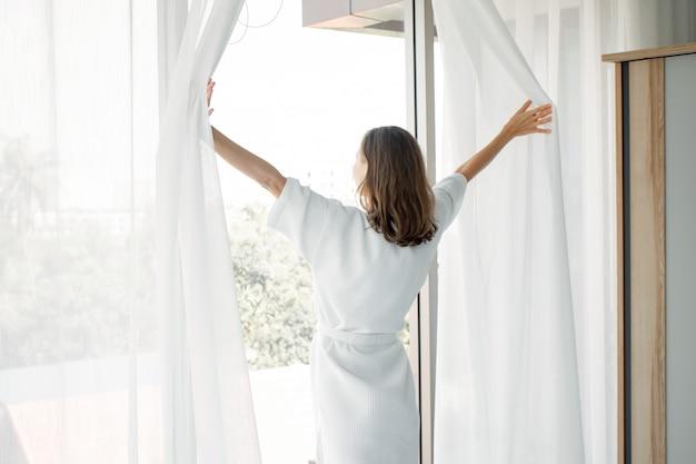 Mujer abre cortinas blancas en la ventana, la mañana después de despertarse.