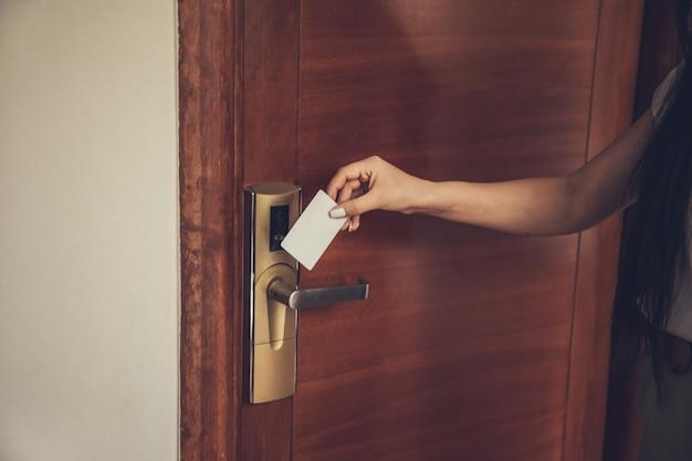 Mujer abriendo la cerradura electrónica de la habitación del hotel con tarjeta llave