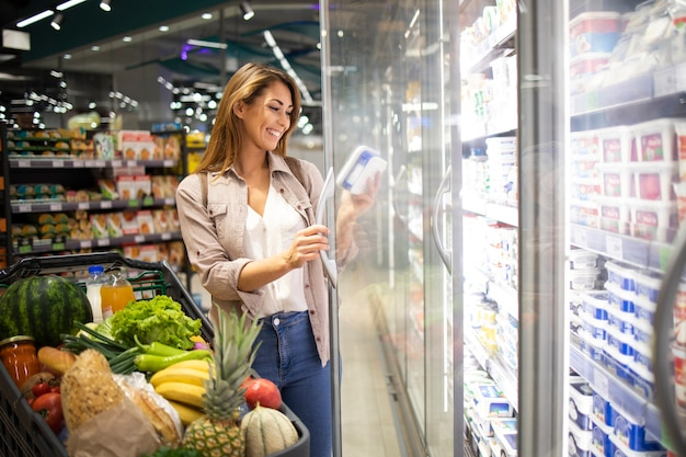 Mujer abriendo la puerta del frigorífico y comprando alimentos en el supermercado