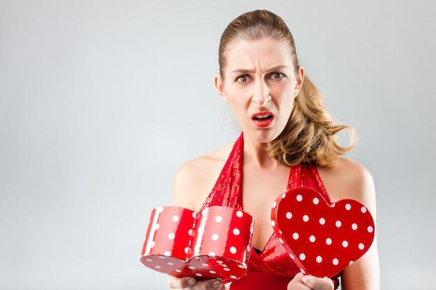 Mujer abriendo el regalo y está decepcionada