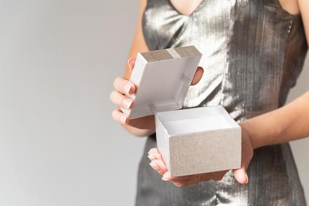Mujer abriendo regalo envuelto en plata