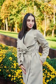 Mujer en un abrigo beige camina en el parque otoño