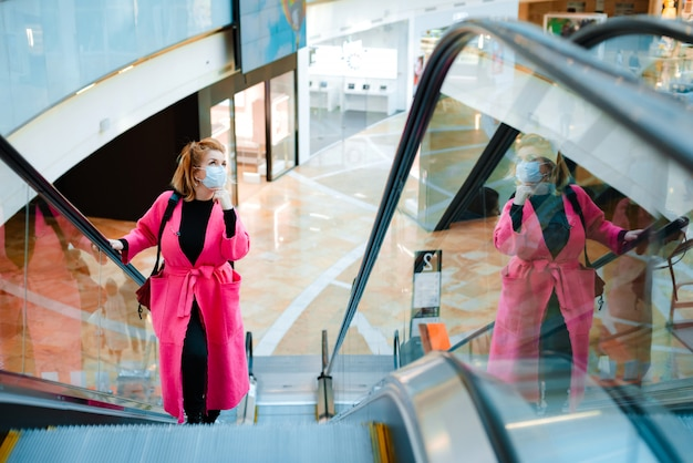 Mujer abrigo brillante monta escaleras mecánicas centro comercial máscara protectora negra en su rostro contra el aire contaminado por el virus.