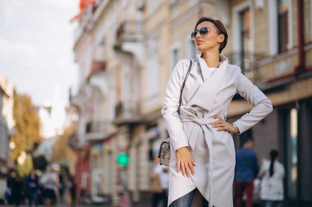 Mujer en abrigo fuera de la calle