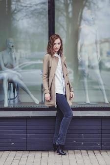 Mujer en un abrigo y jeans cerca del centro comercial