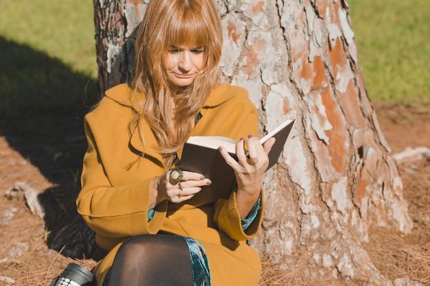Mujer en abrigo leyendo debajo de árbol