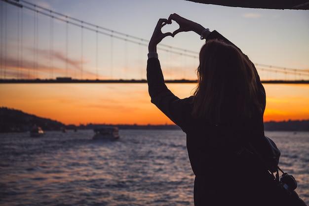 Mujer en abrigo oscuro de pie con las manos en alto haciendo un corazón con el bósforo y la vista del puente en el fondo al atardecer