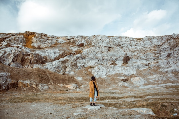 Mujer en un abrigo de pie en las montañas rocosas en un día de otoño