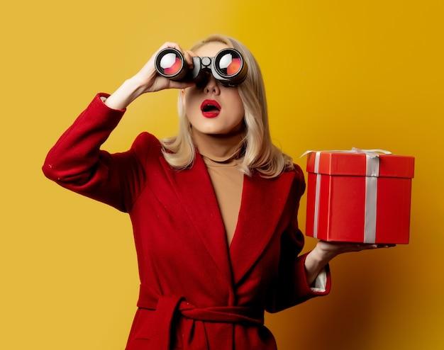 Mujer de abrigo rojo con binoculares y caja de regalo en la pared amarilla