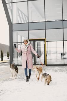 Mujer con un abrigo rosa, perros paseantes