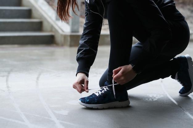 Una mujer se abrocha los cordones de los zapatos. persona atando cordones de los zapatos.