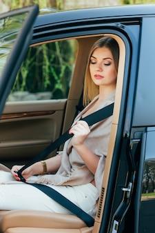 Mujer abrocharse el cinturón de seguridad en un coche