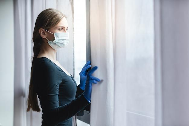 Mujer aburrida en cuarentena corona mirando por la ventana