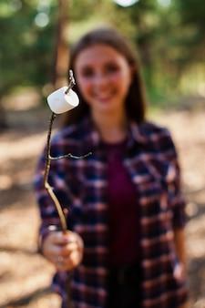 Mujer acampando y cocinando marshmellow