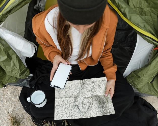 Mujer acampando y mirando en el mapa