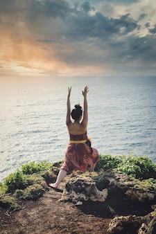 Mujer en un acantilado con vistas al mar hace saludo al sol