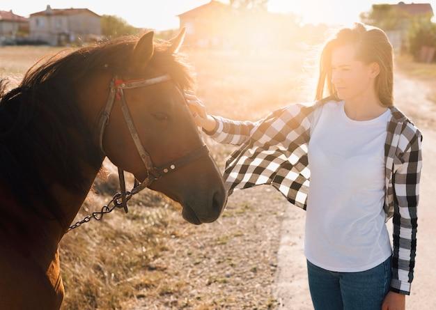 Mujer acariciando adorable caballo