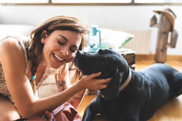 Mujer acariciando a su perro en casa.