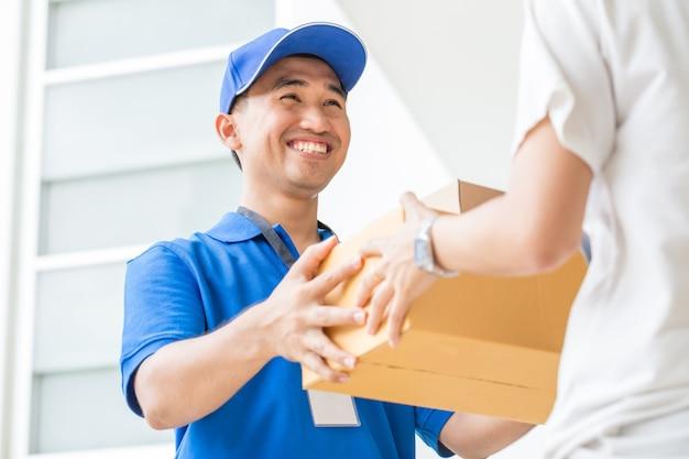 Mujer aceptando una entrega de cajas de cartón del repartidor