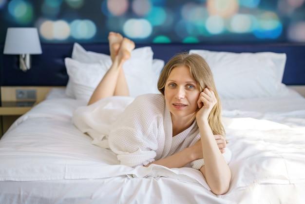 La mujer está acostada en una bata en la cama,