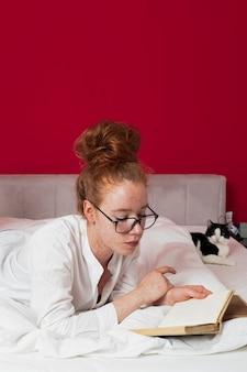 Mujer acostada en la cama con gato leyendo