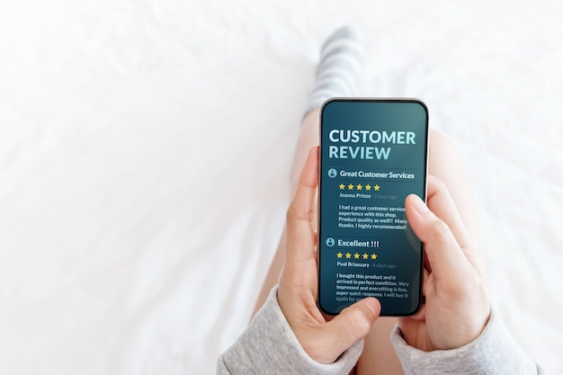 Mujer acostada en la cama para leer la reseña en línea a través de un teléfono inteligente
