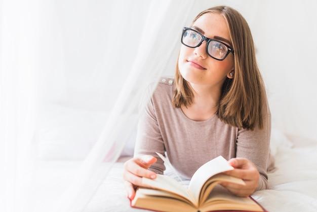 Mujer acostada en la cama con el libro soñando despierto
