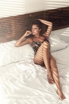 Mujer está acostada en la cama por la mañana